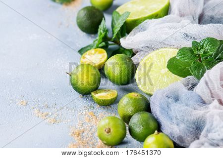 Ingredients for mojito cocktail, whole, sliced lime and mini limes, mint leaves, brown crystal sugar over gray stone texture background with gauze textile. Copy space. Close up
