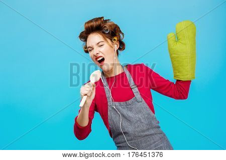 Cute girl sings songs in spoon listening to music while cooking at blue kitchen