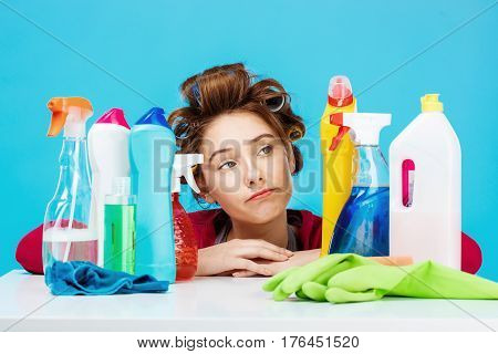 Young beautiful woman with curlers on head looks tired after cleaning house