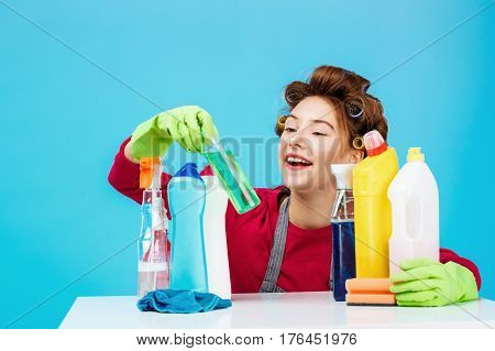 Interested young girl with curlers on hair checks bottle and smile while laundry