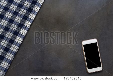 Smartphone and fabric of grid pattern on dark wooden table
