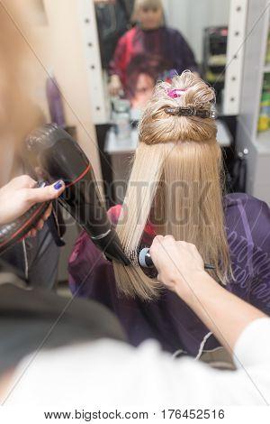 Styling female hair dryer in the beauty salon