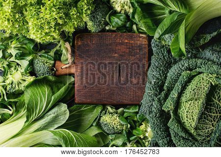 Variety of raw green vegetables salads, lettuce, bok choy, corn, broccoli, savoy cabbage round empty wooden chopping board. Food background. Top view, space for text
