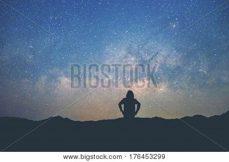 Long exposure Man standing along the waters edge under the Milky Way galaxy