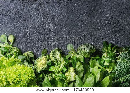 Variety of raw green vegetables salads, lettuce, bok choy, corn, broccoli, savoy cabbage as frame over black stone texture background. Top view, space for text