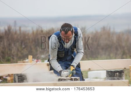 Building working - adult man with circular saw outdoors, small business, telephoto shot