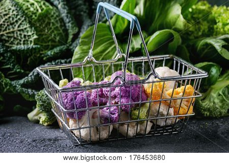 Variety of raw green vegetables salads, lettuce, bok choy, corn, broccoli, savoy cabbage, colorful young cauliflower in shop basket. Black stone texture background.