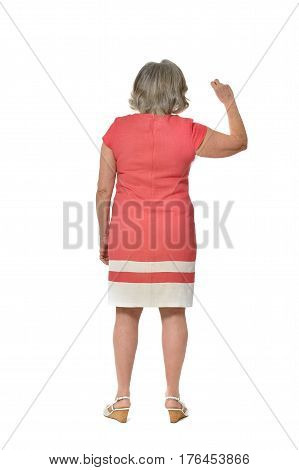 Full length portrait of senior woman in red dress, back view on white background