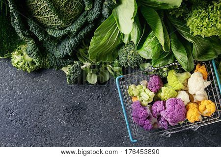 Variety of raw green vegetables salads, lettuce, bok choy, corn, broccoli, savoy cabbage, colorful young cauliflower in shop basket. Black stone texture background. Top view, space for text