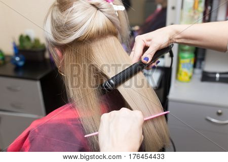 Stylist puts women's hair on a plate .