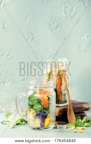 Variety of vegetable salads in mason jars. Salad with greens, pasta, carrots, cauliflower, salmon. Standing with wooden spoon and serving board over blue texture background. Healthy food to go.