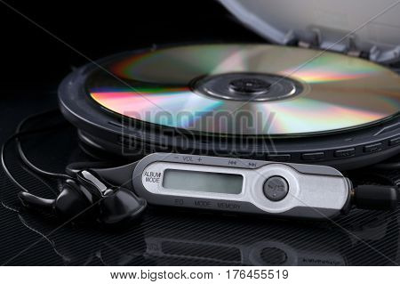 Opened personal cd player with remote control and portable audio earphones on black background