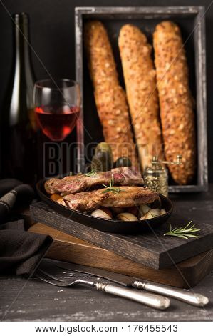 Grill pork steak on an old rustic wooden chopping board in a country kitchen with red wine and french baguette on wooden black background. Pork steak in low key