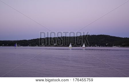 Sailboats are seen in distance in the Halifax Harbor late in the afternoon in Halifax Nova Scotia on a sunny day in September