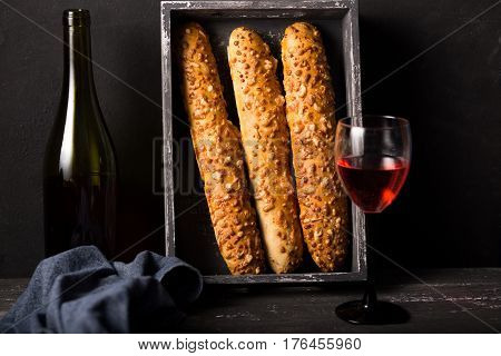 French cheese baguette with a red wine.Homemade freshly baked french baguettes. rustic style. long bread.