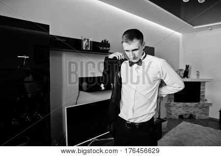 Man Wearing Bow Tie Wear Jacket, Morning Of Groom At Wedding Day. Black And White Photo