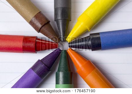 Assorted crayons on a blank lined paper sheet