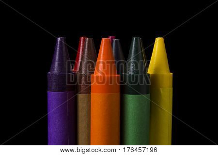 Close up of colorful crayons isolated on a black background