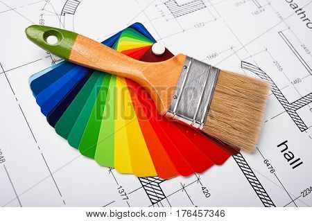Construction of the building layout, building drawing on paper, paint brush and color samples, selecting paint colors, construction planning