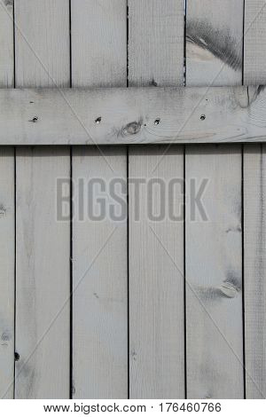 Vertical image of wood background, with grain bleeding through  stain and exposed nails.