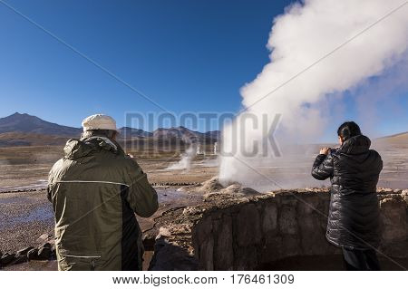 Geysers del Tatio Chile - November 24 2013: Tourists watching a geyser in the Geysers del Tatio field in the Atacama Desert Northern Chile