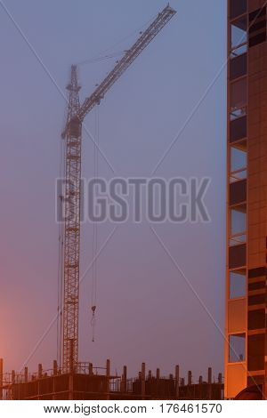 Construction crane on the site, unfinished house, fog covers the upper floors, evening twilight.