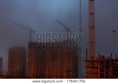 Two cranes on the construction site, unfinished house, foggy evening twilight.
