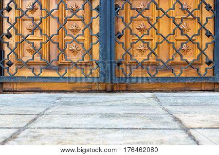 part of the closed wooden gate or door and openwork metal lattice