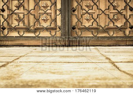 part of the closed wooden gate or door and openwork metal lattice of sepia color