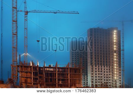 Cranes on a large construction site, unfinished houses, fog covers the upper floors, evening twilight.