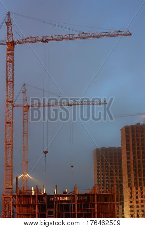 Two cranes on the construction site, unfinished multi-storey house, foggy evening twilight, building lighting.