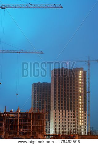 Two cranes on the construction site, unfinished multi-storey house, foggy evening twilight, the lighting of the floors.