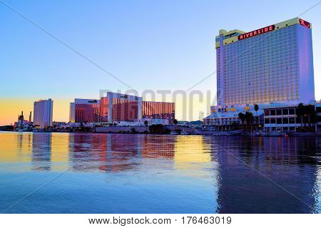 March 1, 2017 in Laughlin, NV:  Hotel Casinos on the Riverfront Boardwalk beside the Colorado River taken in Laughlin, NV where tourists can walk the boardwalk and gamble while viewing the Colorado River during dusk