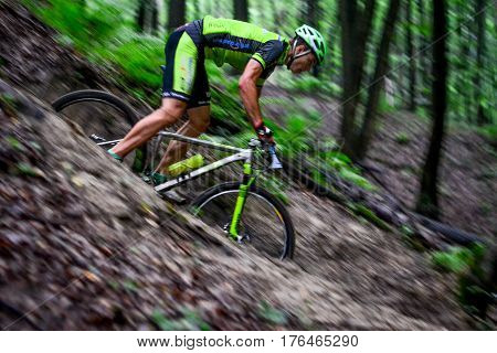 Lviv Ukraine - August 17 2016: MTB cyclist E. Zakora competing in the forest near Lviv in Ukraine at 4th round of amateur xc cup of Ukraine 2016.