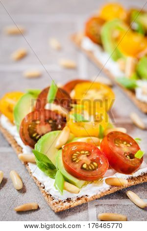 Сrisp Bread Toast  With Cream Cheese, Fresh Avocado, Cherry Tomatoes And Pine Nuts