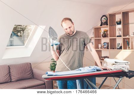 Handsome Man Ironing Shirt At Home