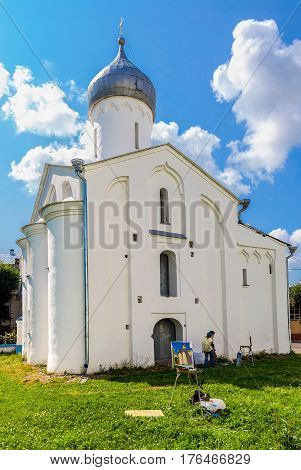 NOVGOROD RUSSIA - JULY 23 2014: Young artists paint at the walls of an ancient cathedral at the Yaroslav's Court in Veliky Novgorod