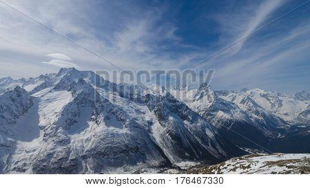 Cold snow caucasian spring mountains. Dombai, Russia.