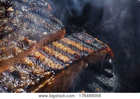 Steak salmon in a frying pan in a smoke and steam