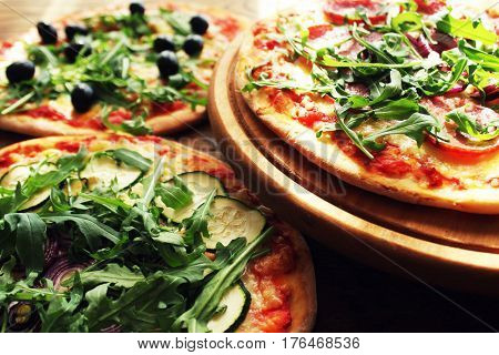 Different variations of pizza.Pizza with sausage, zucchini, olives, cheese rucola. Top view