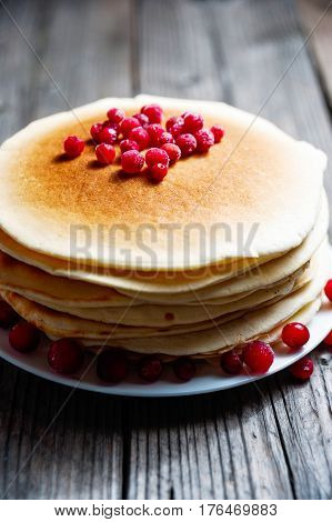A Stack Of Pancakes With Cranberries On A White Plate On A Wooden Boards Background