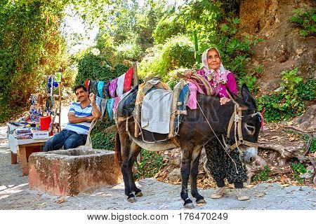 Antalya Turkey - 26 august 2014: An old Turkish woman and a saddled donkey are standing next to a roadside trader on a mountain road.
