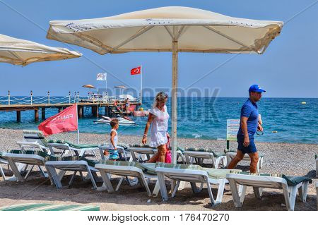 Antalya Turkey - 29 august 2014: A family of three people walks along a deserted beach.