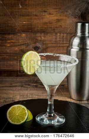 Alcoholic cocktail - gin tonic martini margarita. Decorated with slice of lime with a shaker on a black slate on a wooden table copy space vertical