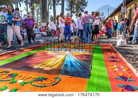 Antigua, Guatemala - March 25 2016: Locals admire handmade dyed sawdust Good Friday carpet for procession. Agua volcano is behind in colonial town with most famous Holy Week celebrations in Latin America.