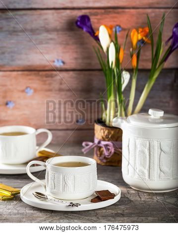 White Cup of tea. The tea party. Chocolate on the saucer. Pot of flowers in the background. Selective focus. Wooden background