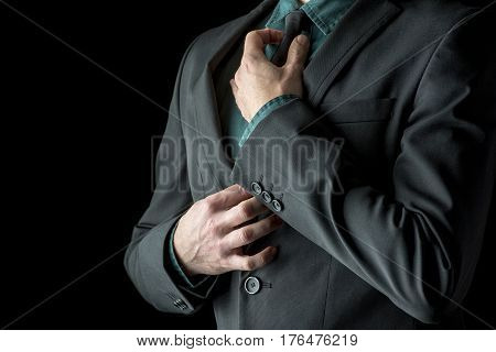 Businessman In Green Shirt And Suit Adjusting His Black Necktie