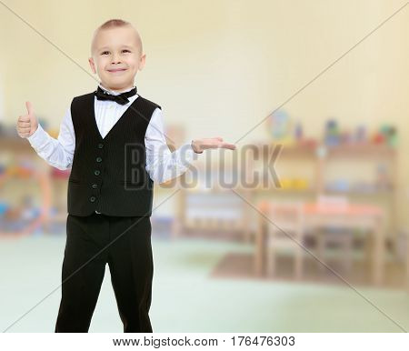 Beautiful little blond boy in a fashionable black suit with a bow tie. He shows his hand to the side. In the Montessori room the children's garden where there are shelves with toys and material.