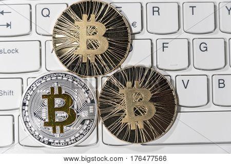 Shining metal BTC bitcoin coins on white computer keyboard.