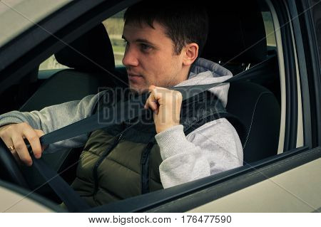 Driving Safety. A Young Man Fastens The Seat Belt